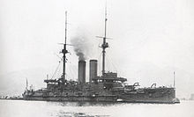 Large warship with smoke rising from the smokestack