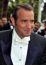 A man wearing a black suit including a white shirt and bow tie.