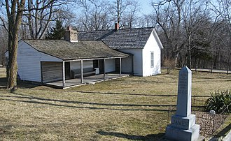 James–Younger Gang - Jesse James Farm in Kearney, Missouri. The original farmhouse is on the left and an addition on the right was expanded after Jesse James died. Across a creek and up a hill on the right was the home of Daniel Askew who was killed at home on April 12, 1875. Askew was suspected of cooperating with the Pinkertons in the January 1875 bombing of the house (in a room on the left). James' original grave was on the property but he was later moved to a cemetery in Kearney. The original footstone is still outside although the family has replaced the headstone.