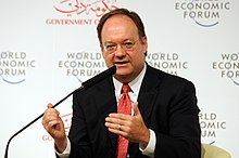 A bald middle aged man in a suit at a table speaks into microphone. Behind him several signs read World Economic Forum.