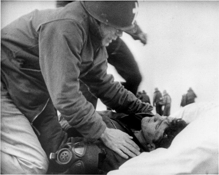 Joseph T. O'Callahan gives last rites to an injured crewman aboard USS Franklin (CV-13), 19 March 1945
