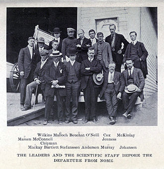 A group of 16 men, standing or sitting, on the deck of a ship with a small lifeboat visible, left background. The group's pose is casual and the men are variously attired, many in suits with casual hats of different sorts.