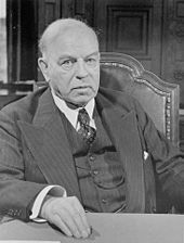 An older man in a three piece suit, seated and looking at the camera