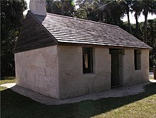 Color photo of the outside of a 2-room cabin covered in stucco, with a wood-shingle roof overtop and a chimney. One doorway in the middle of the longer wall indicates an entrance, and two glassless windows are located on both sides of the door.
