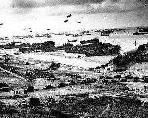 "USS LST-310 - LST-310 (2nd LST from the right) along with other ships putting cargo ashore on one of the invasion beaches, at low tide during the first days of the Invasion of Normandy in June, 1944. Among identifiable ships present are LST-532 (in the center of the view); LST-262 (3rd LST from right); LST-533 (partially visible at far right); and LST-524. Note the barrage balloons overhead and Army ""half-track"" convoy forming up on the beach."