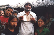 A Bhutanese man standing next to several children is depicted showing the camera his passport.