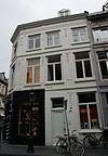 foto van Hoekhuis, waarvan de lijstgevels (uit drie gedeelten, die met elkaar stompe hoeken maken) voorzien van vensters in Naamse steen, gescheiden zijn door verdiepte panelen met festoenen.