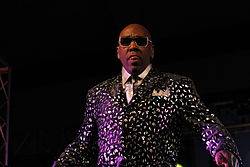 Wanz wearing sunglasses and a colorful suit