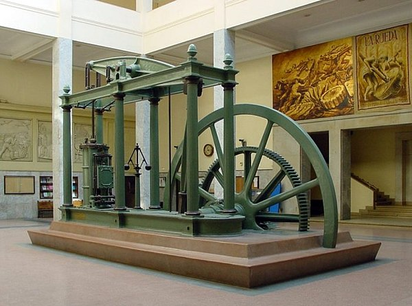 A late version of a Watt double-acting steam engine, built by D. Napier & Son (London) in 1859, now in the lobby of the Superior Technical School of Industrial Engineers of the UPM (Madrid). Steam engines of this kind propelled the Industrial Revolution in Great Britain and the world. Maquina vapor Watt ETSIIM.jpg