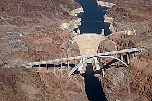 The bridge is silhouetted against the sky with the Colorado river far below