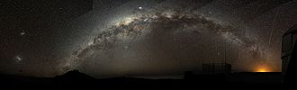 Milky Way - The Milky Way arching at a high inclination across the night sky. (This composited panorama was taken at Paranal Observatory in northern Chile). The bright object is Jupiter in the constellation Sagittarius, and the Magellanic Clouds can be seen on the left. Galactic north is downward.