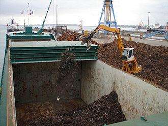Bulk cargo - A mini-bulker taking on scrap iron cargo in Brest, France.