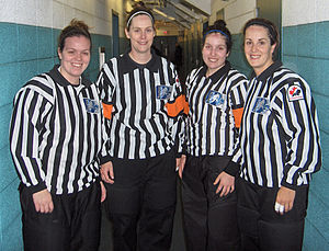 Official (ice hockey) - These female officials are working in a four-official system; the two middle officials are the referees, identifiable by their orange armbands