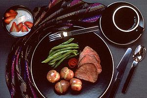 A dinner is set up on black, gold-rimmed dishe...