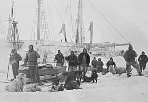 A group of men pose on the ice with dogs and sledges, with a ship's outline visible in the background