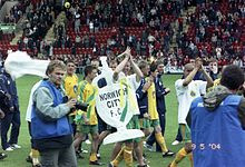 Footballers celebrating with a large cardboard fake trophy