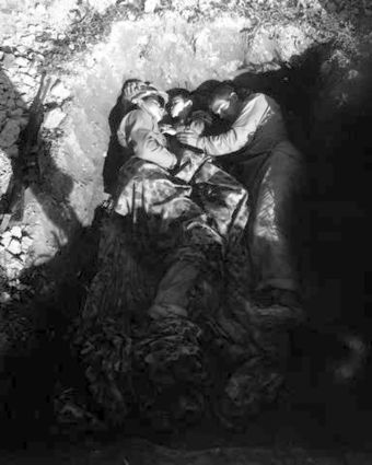 Two US Marines share a foxhole with an Okinawan war orphan in April 1945. OkinawaMarineOrphan.jpg