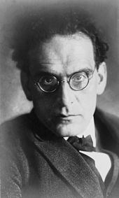 head and shoulder image of man with dark hair and spectacles, glaring towards the camera