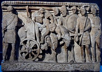 Volterra - Menelaus and Meriones lifting Patroclus' corpse on a cart while Odysseus looks on; alabaster urn, Etruscan artwork from Volterra, 2nd century BC