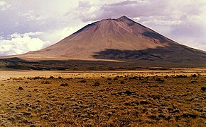 A conical mountain rising above yellow vegetation