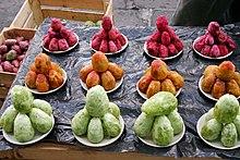 Des figues de barbarie pelées, de couleur verte, jaune ou rouge, empilées dans des coupelles sur une étale de marché