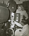 R.J. (Bob) Lucas and unidentified woman looking at a Centrex projector, 1940 - 1949 (4436758030).jpg