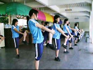 Warming up - A group of High School girls performing a ballistic stretch in a Physical Education session
