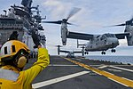Sailor directs an MV-22B Osprey as it takes off from the flight deck of USS Iwo Jima. (33282531096).jpg