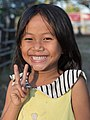 Smiling young girl with yellow shirt giving V-sign.jpg
