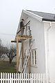 Snekker setter inn nytt vindu på et stillasje av tre 1.JPG