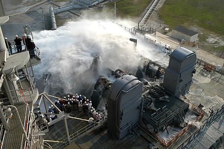 A test of the sound suppression system test in 2004. During launch, 350,000 US gallons (1,300,000 L) of water are poured onto the pad in 41 seconds. Sound suppression water system test at KSC Launch Pad 39A.jpg