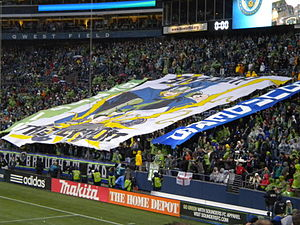 "Fans in a stadium display a large banner. In the center is a picture of Thor wearing a green jersey and smashing the Union logo. It reads ""Smash the Union"" in the center, ""Seattle"" vertically on the left, and ""Sounders"" on the right."