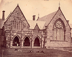 1870s photograph of church-like stone building, with students lying on the grass in front
