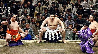 Makuuchi - Yokozuna Asashōryū (center) performing the ring-entering ceremony while flanked by a sword bearer on the left and dew sweeper on the right
