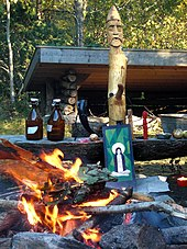 An outdoor fire burns in front of a wooden post with an anthropomorphic face carved into the top.