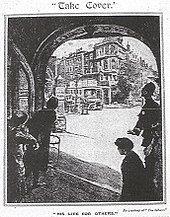 Women hiding in a wide darkened doorway. They look out through the building at a street, deserted except for a single policeman who gestures for them not to leave the building.