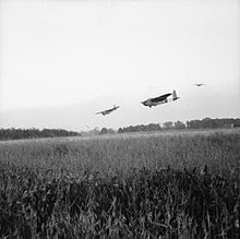 Large gliders in the sky, preparing to land in a field