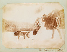 Salt print photograph of a man and woman building a snow man, circa 1853