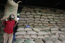 A man carries a large bag on his shoulders.  Behind him, thousands of bags are stacked in rows.