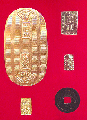 Tokugawa coinage - Main coins of Tokugawa coinage. A large ovoid gold Koban, under it a small gold Ichibuban, top  right a silver Ichibuban, under it a silver Isshuban and a bronze round Mon.