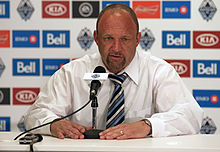 A Caucasian man with a shaved head dressed in a white shirt and striped tie sits at a table with his hands holding the base of a microphone and looks downward from the middle of the picture. Behind him are logos of various companies that sponsor the Vancouver Whitecaps.