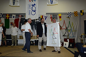 2012 Vintage Yachting Games - The Vintage Flag was transferred from Carlo Bossi and Pietro Adamoli (Multilario), via Rudy den Outer (Vintage Yachting Games Organization) to John Best representing the Weymouth and Portland National Sailing Academy, the 2016 host.)