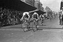 Cyclists crossing a finish line in front of spectators