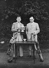 Two men standing next to a table with two golfing trophies