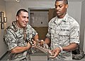 U.S. Air Force Airman 1st Class Ponce Carrillo, left, tries to pull the tail of a ball python from under his shirt as Airman 1st Class Lennell Day handles a Great Plains rat snake July 25, 2011, at Sheppard Air 110725-F-NS900-002.jpg