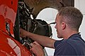 U.S. Coast Guard Avionics Electrical Technician 1st Class Brad Bucklew, assigned to Coast Guard Air Station (AIRSTA) Traverse City, cleans the engine of an MH-65C Dolphin helicopter at Air Facility (AIRFAC) 130731-G-ZZ999-020.jpg