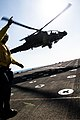 U.S. Navy Boatswain's Mate 2nd Class Jose Rangel signals the pilot of an Army AH-64 Apache helicopter assigned to the 4th Battalion, 227th Aviation Regiment and attached to the 42nd Combat Aviation Brigade 131226-Z-AR422-344.jpg