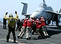 "US Navy 020711-N-2329T-002 Sailors ""push back"" an F-A-18 ""Hornet"" strike fighter aircraft.jpg"
