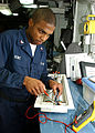 US Navy 020920-N-6433N-001 Electrician's Mate conducts tests in the ship's battery and lighting shop.jpg