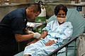 US Navy 060529-N-3931M-028 Navy Hospital Corpsman 3rd Class Lawrence Santos from Stockton, Calif., draws blood from a patient in Casualty Receiving aboard the U.S. Military Sealift Command (MSC) hospital ship USNS Mercy (T-AH 1.jpg